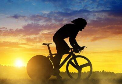 Quadro Silhueta de um ciclista em uma bicicleta de corrida de estrada ao pôr do sol.