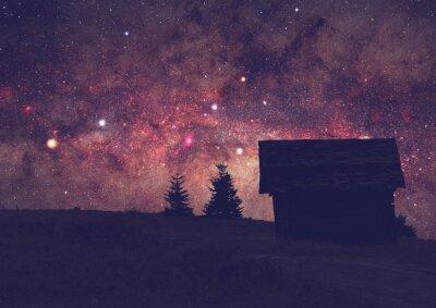 Quadro Silhuetas de um campo com Via Láctea. Foto longa da exposição tomada de uma parte superior escura da montanha.
