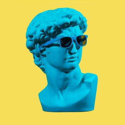 Quadro Statue. Earphone. Isolated. Gypsum statue of David's head. Man. Creative. Plaster statue of David's head in blue sunglasses. Minimal concept art.