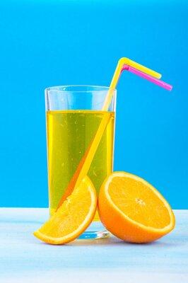 Quadro Suco de laranja em um copo com palhas coloridas e fatias de laranja em um fundo azul