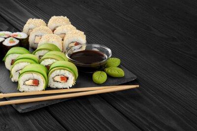 Quadro Sushi rola com sementes de abacate, salmão e gergelim na bandeja de ardósia.