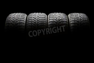 Quadro Tiro de estúdio de um conjunto de quatro pneus de carros pretos alinhados horizontalmente em um ambiente escuro no fundo preto