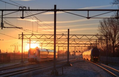 Quadro Trains leaving a station during a winter sunrise.