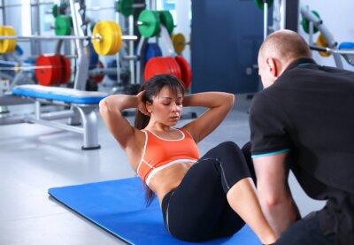 Quadro Uma jovem mulher com seu treinador na academia