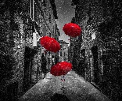 Quadro Umrbellas voando com vento e chuva na rua escura em uma antiga cidade italiana em Toscana, Itália