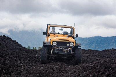 Quadro Visão frontal de um condutor de cabelos cacheados em um veículo offroad amarrado estacionado no topo de um vale com rochas vulcânicas e montanhas em Bali, na Indonésia