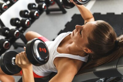 Quadro Woman lifting  weights and working on her chest at the  gym