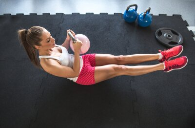 Quadro Woman working on her abs with kettlebell